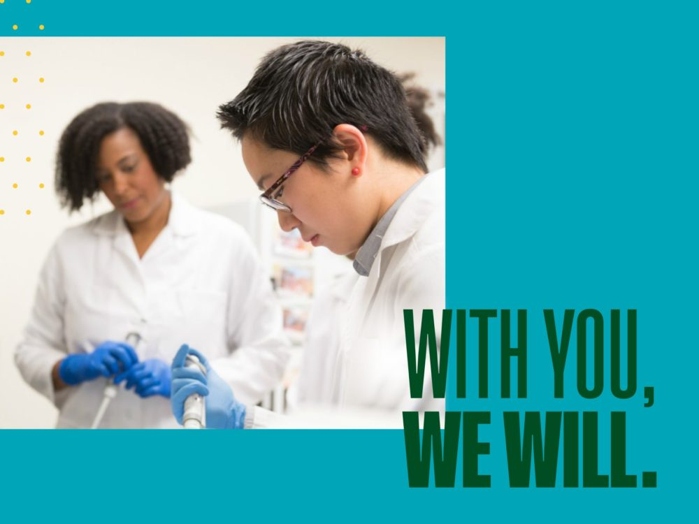 Students in a lab with text `With You, We Will.`