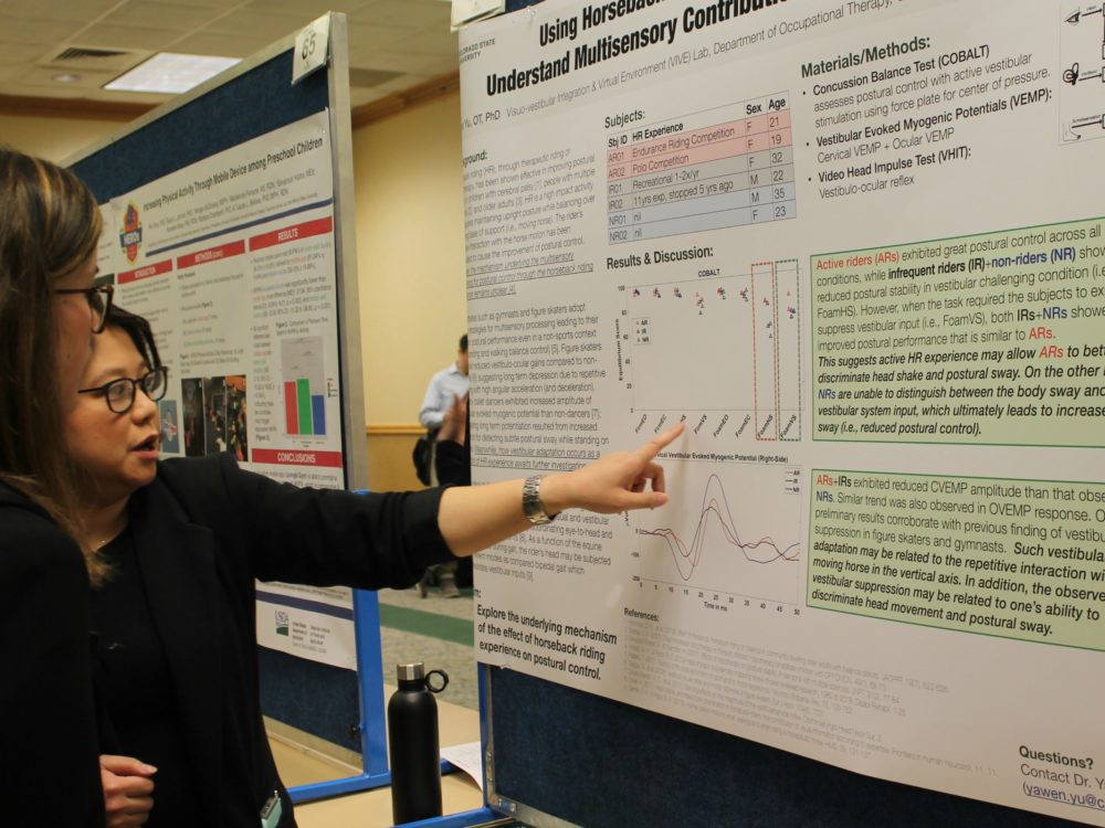 Yawen Yu explaining her research poster to a visitor