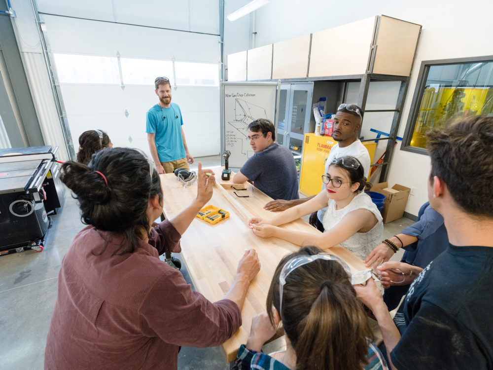 An instructor and his students discussing their work in the Wood Lab