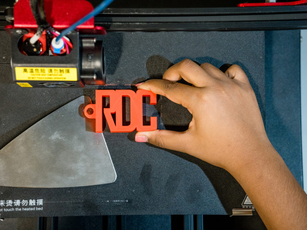 A hand holding an orange 3D printed block of letters reading `RDC`