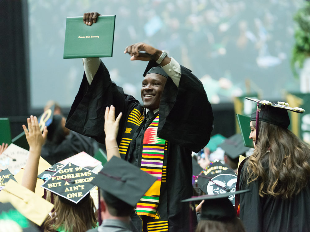 CHHS student holds up diploma at commencement ceremony