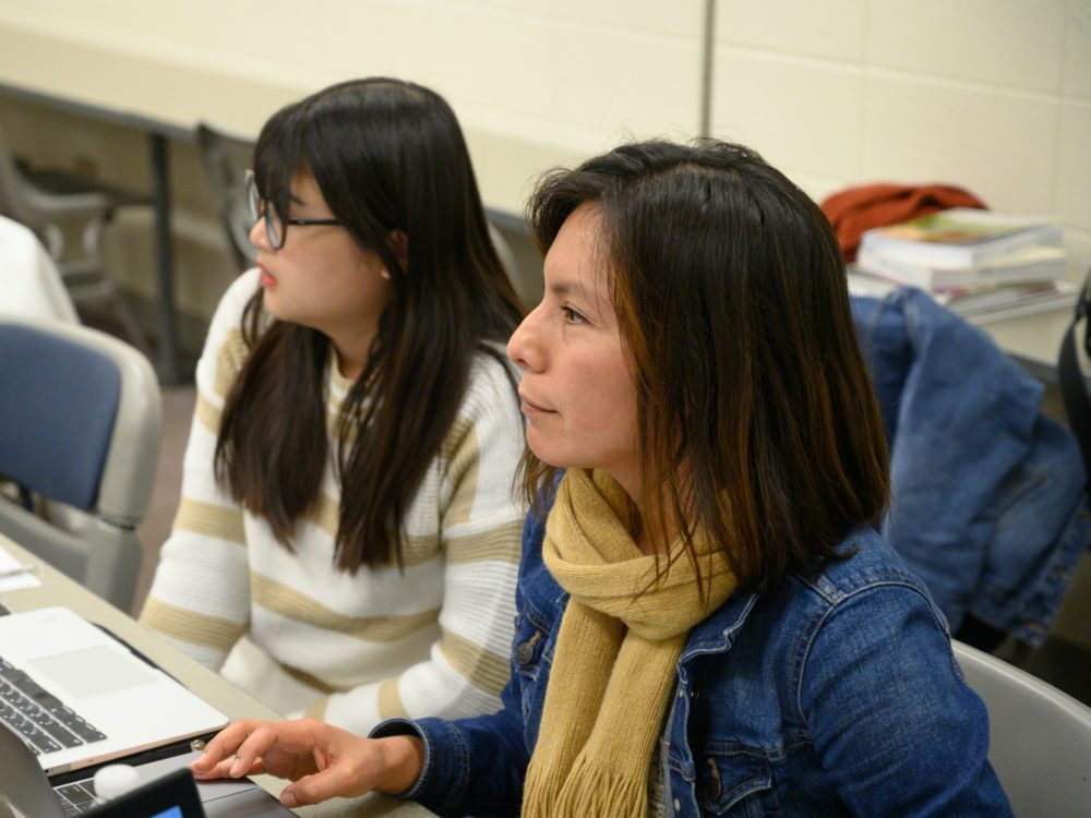 Two students, both presenting as Asian women, listen during class