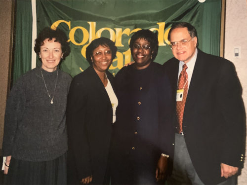 Cheryl Presley smiles in front of a Colorado State University banner with colleagues.